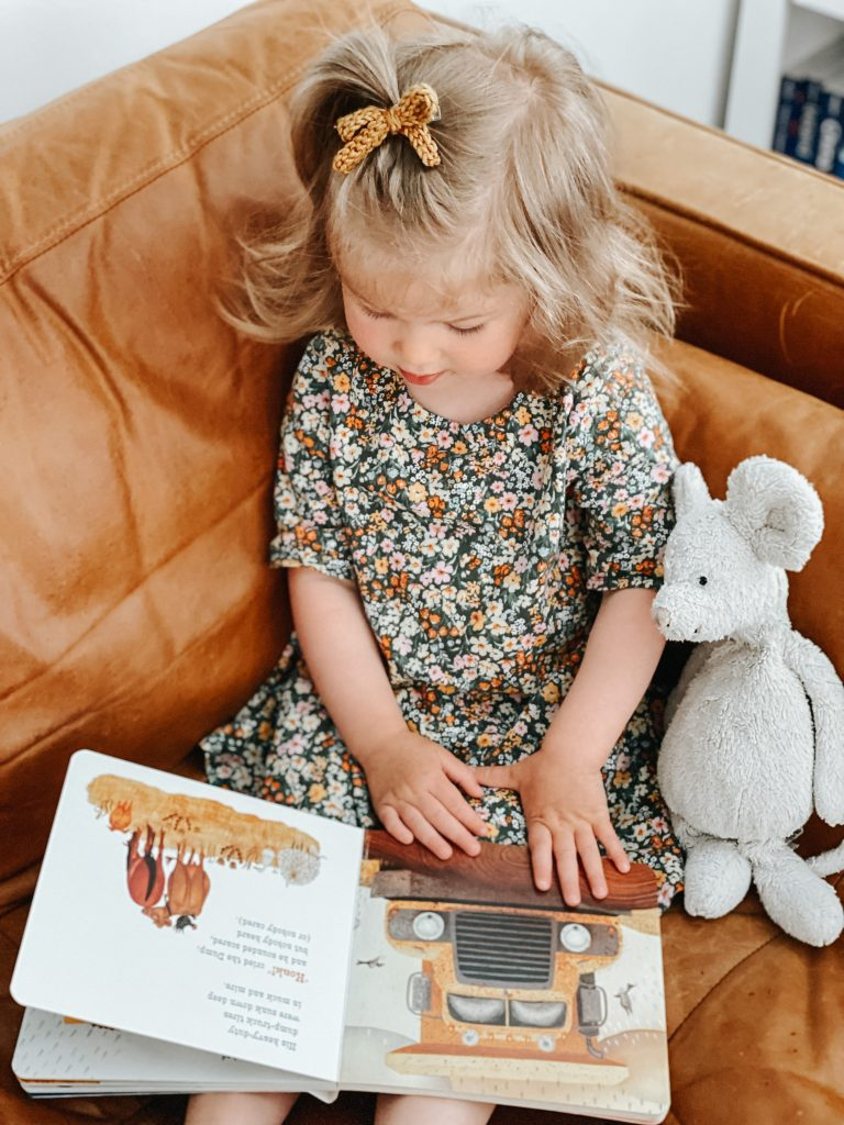 Little girl reading a book with her mouse stuffed animal.